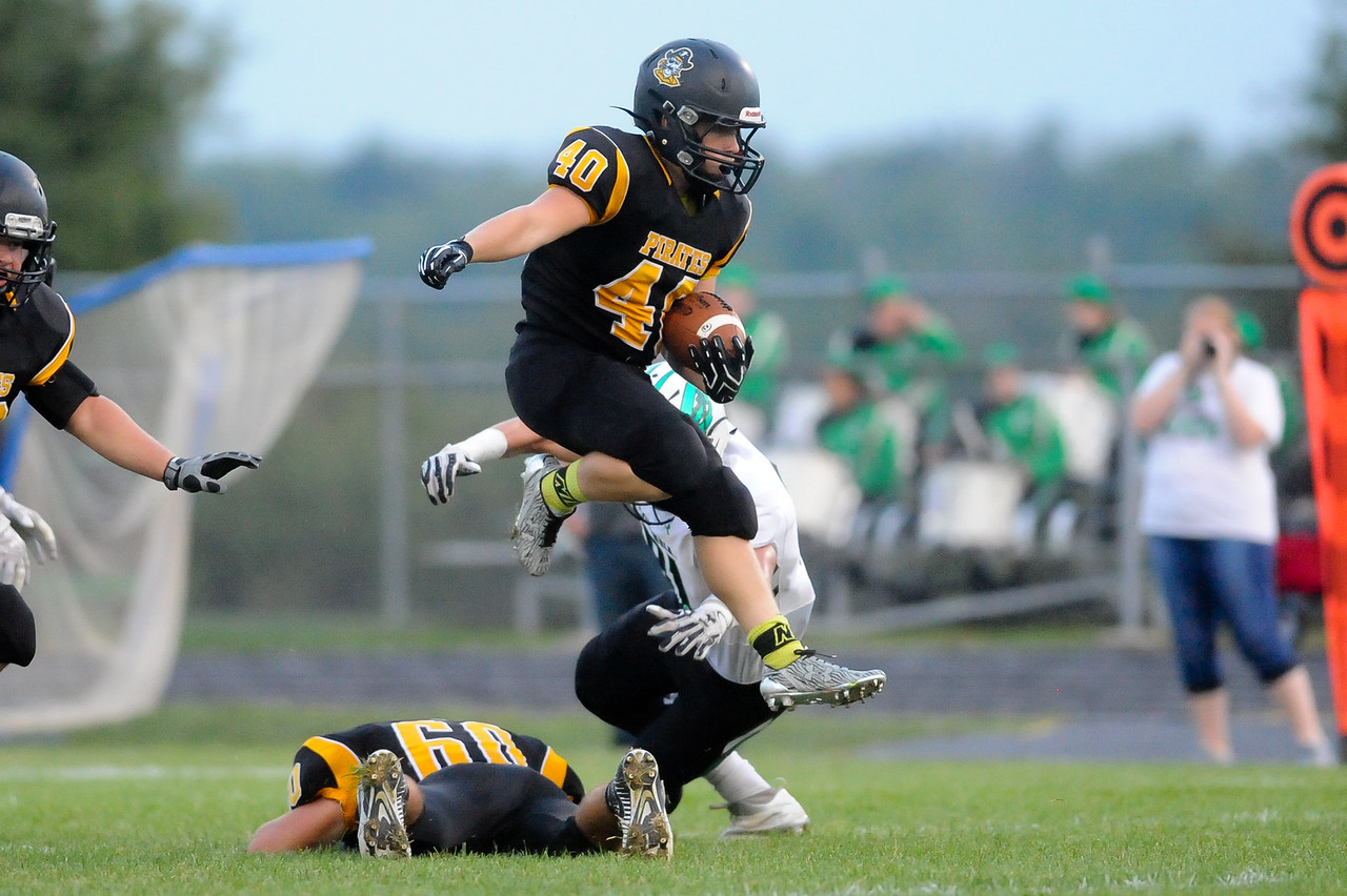 Black River's Cory Bartolic leaps over teammate Cole Haswell and avoids the tackle of Columbia's Lance Boise as he runs for a 53 yard touchdown in the first quarter. (JUDD SMERGLIA / GAZETTE)