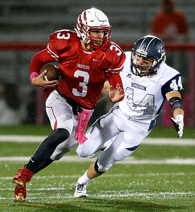 Wadsworth quarterback Joey Baughman runs away from Hudson's Daniel Saxon during the first quarter. (RON SCHWANE / GAZETTE)