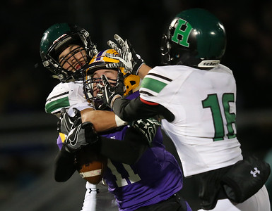 Highland defenders Jake Rogers (L) and Ryan Frederick break up a pass intended for Avon receiver Chris Mullins in the second quarter. Aaron Josefczyk/Gazette Photo