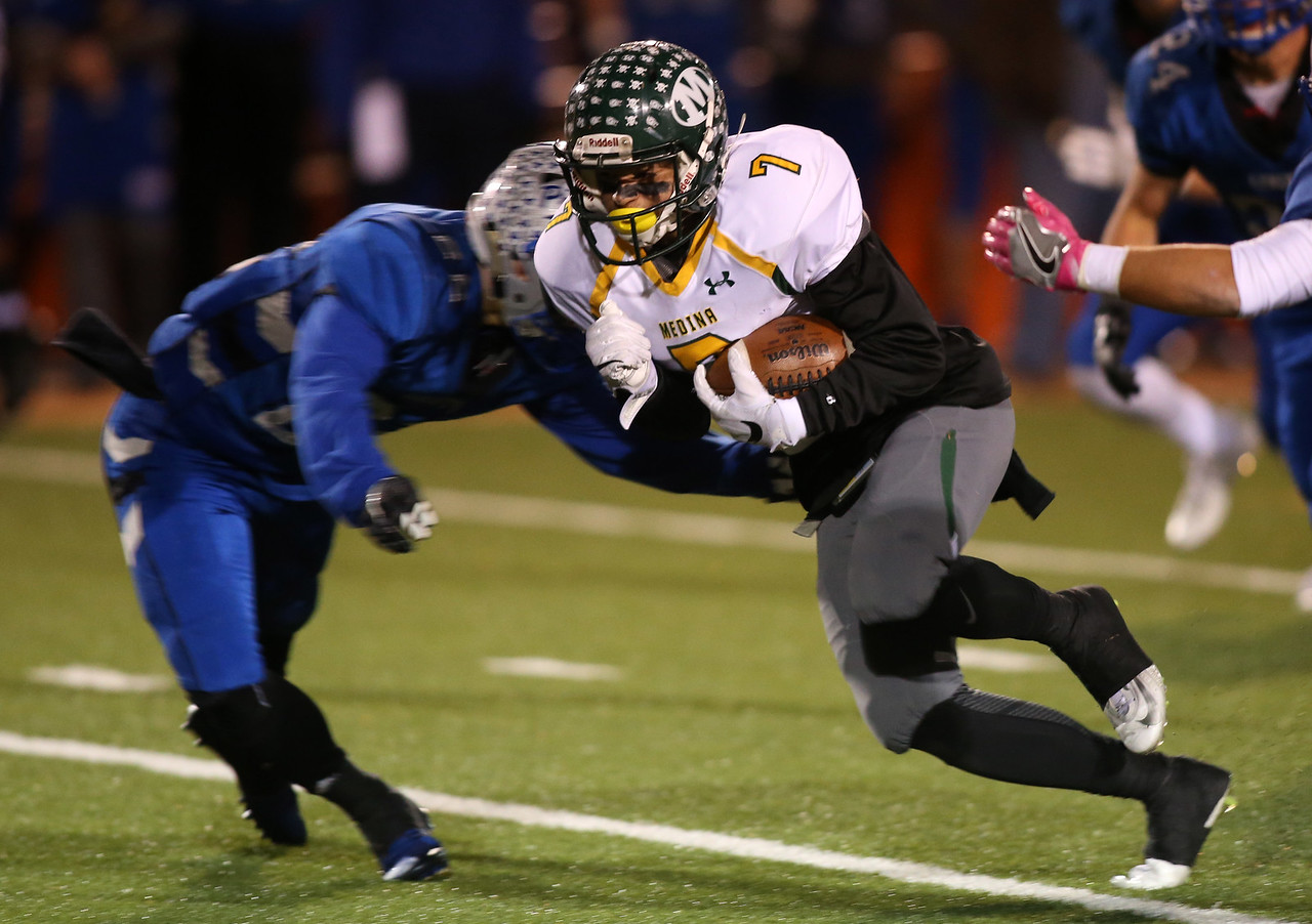 Medinas' Dylan Fultz runs after making a catch in the third quarter as he is hit by Olentangys' James Vivona during their playoff game in Mansfield. AARON JOSEFCZYK / GAZETTE