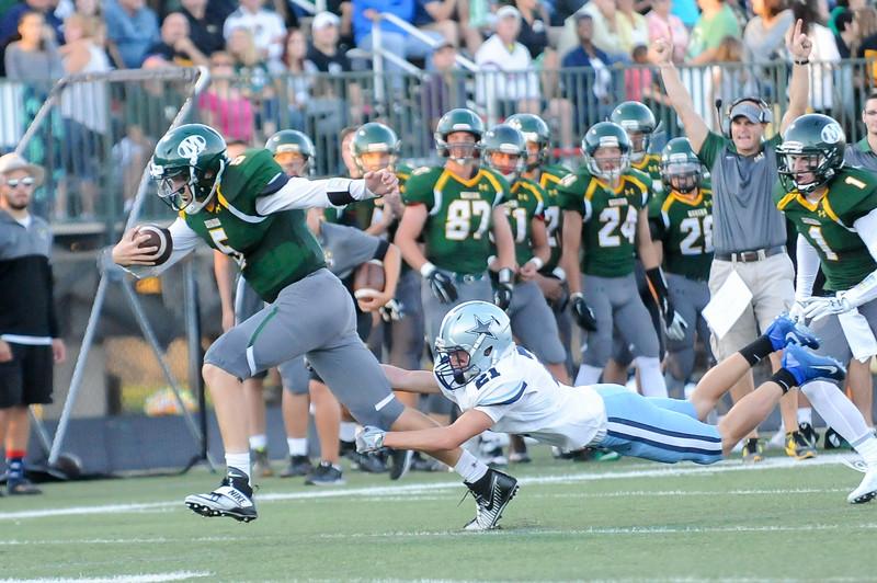 Medina quarterback John Curtis (5) runs away from the tackle of Kenston's Michael Swartz (21) for a touchdown in the second quarter Friday night. (JUDD SMERGLIA/GAZETTE)