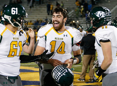 Medina's Jimmy Daw (14) celebrates with Jacob Shoemaker (61) and Nick Chester after beating Whitmer 38-31. (RON SCHWANE / GAZETTE)