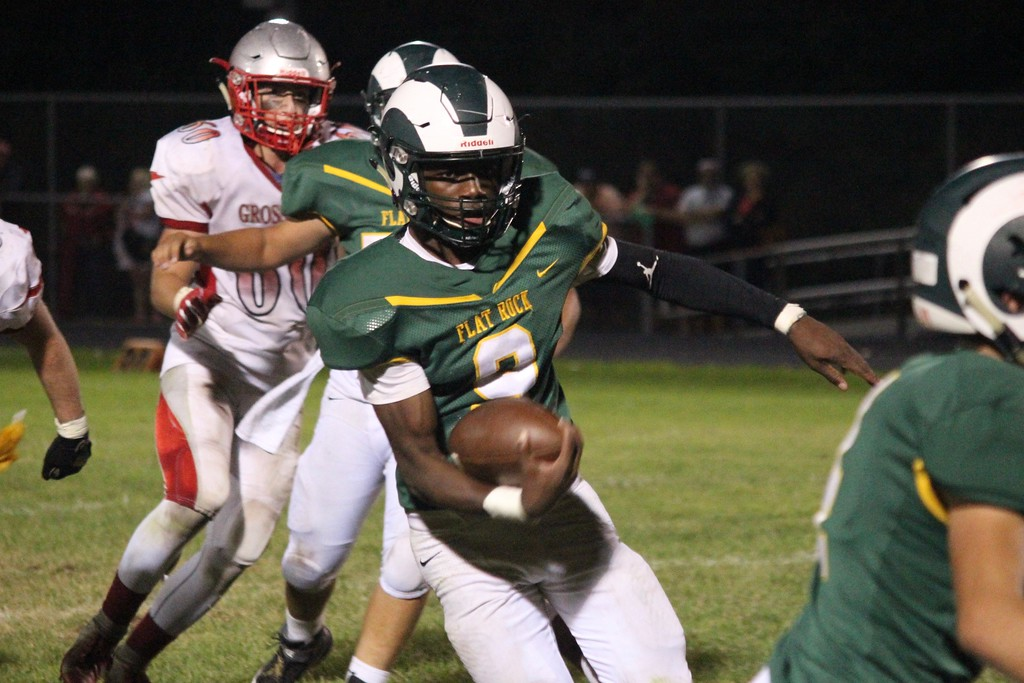 . Flat Rock quarterback Ravion Davis takes off on a run during Friday night\'s game against visiting Grosse Ile. Davis accounted for 232 yards of offense and two touchdowns in what was 33-28 defeat.  Ricky Lindsay - For Digital First Media