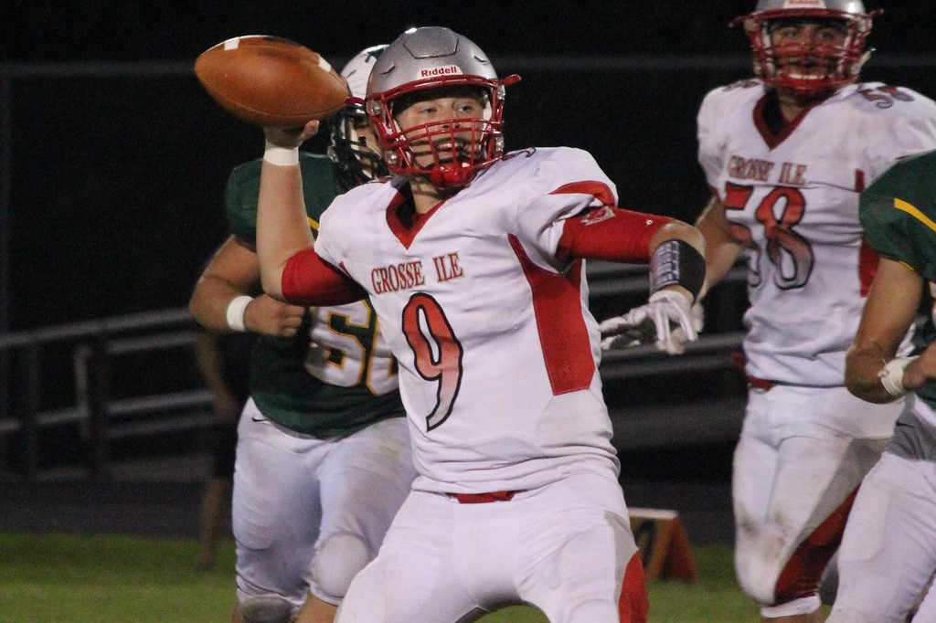 . Grosse Ile quarterback Zak Thompson gets ready to throw during his team\'s 33-28 victory at Flat Rock on Friday night. Thompson threw for 254 yards and three touchdowns and also ran for a score. Ricky Lindsay - For Digital First Media