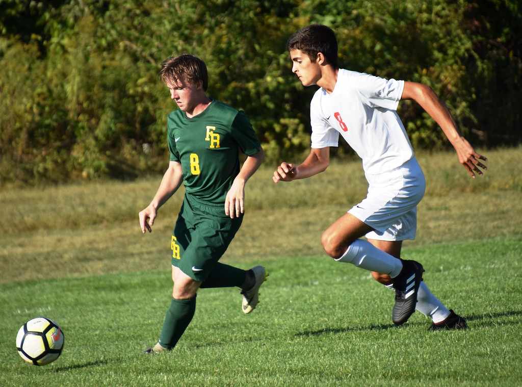 . Andrew Jamison of host Flat Rock (right) is pursued by Remington Emelian of New Boston Huron during Monday\'s Huron League matchup. The Rams went on to suffer a 5-0 defeat against the second-place Chiefs. Alex Muller - For Digital First Media