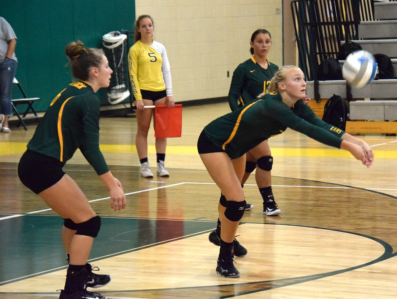 Flat Rock's Carly Doros plays the ball on Monday night, with teammates Ryley Osentoski (left) and Courtney Woods close by. The host Rams defeated the Riverview Pirates 3-2 (22-25, 25-18, 11-25, 25-21, 15-13). Alex Muller - For Digital First Media