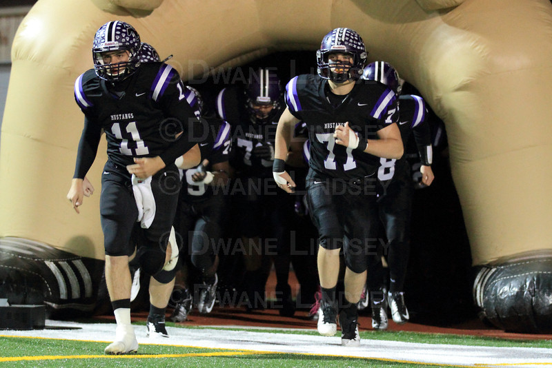 Quarterback Jack Milas (11) of Rolling Meadows leads the team out of the (Mustang) tunnel.
