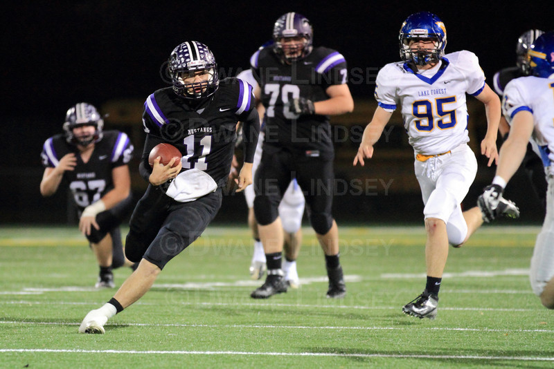 Quarterback Jack Milas (11) of Rolling Meadows runs downfield and eyes up the defensive player.