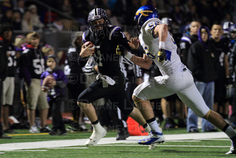 Quarterback Jack Milas (11) of Rolling Meadows attempts to stiff-arm the defensive player before going out of bounds.