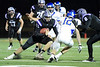 Quarterback Jack Milas (11) of Rolling Meadows tries to avoid the defensive player.