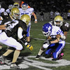CARL RUSSO/Staff photo. Haverhill defeated Methuen 41-20 in Friday night football action. Haverhill's Stephane Bristol (24) tackles Methuen's William Weinhold from behind as Haverhill defenders move in to assist. 10/26/2012.