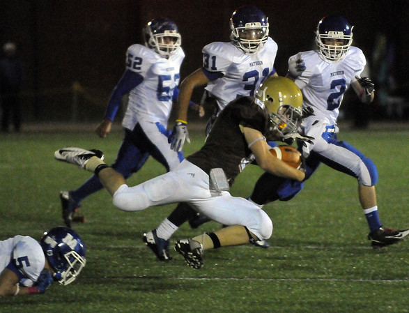 CARL RUSSO/Staff photo. Haverhill defeated Methuen 41-20 in Friday night football action. Haverhill's Matthew Serra (8) is tripped-up and tackled by Methuen's Christian Monserrat (left) as he looks for running room. 10/26/2012.