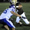 CARL RUSSO/Staff photo. Haverhill defeated Methuen 41-20 in Friday night football action. Haverhill's Shain Roche (5) tries to avoid the tackle by Methuen's Nick D'Avolio (56) as he looks for running room. 10/26/2012.