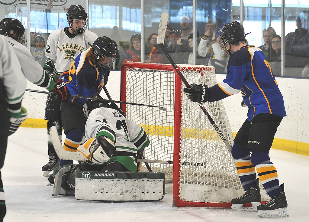 Justin Sheely   The Sheridan Press<br /> Sheridan's Wade Jacobs, left, scores a tie-breaker late in the third period against Laramie during the WAHL High School B State Championship at Whitney Ice Rink in the M&M's Center Sunday, Feb. 25, 2018. The Hawks beat Laramie 4-3 to claim their first state title in 12 years.
