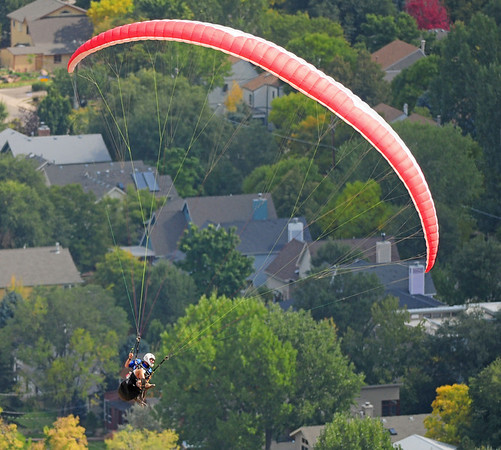 ParaSoft Paragliding School instructor Granger Banks, of Boulder, flies above the residential area near the North Boulder Community Park on Tuesday, Sept. 29, 2009.<br /> Photo by Jeremy Papasso / The Camera / Sept. 29, 2009