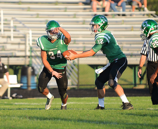HALEY WARD | THE GOSHEN NEWS <br /> Concord quarterback Jack Lietzan hands off the ball running back Dominick De Broka during the game against Saint Joseph Friday at Concord High School.