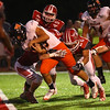 JAY YOUNG | THE GOSHEN NEWS<br /> Warsaw High School quarterback Tristan Larsh fights off Goshen High School defenders to score a third quarter touchdown during their game Friday night at GHS.
