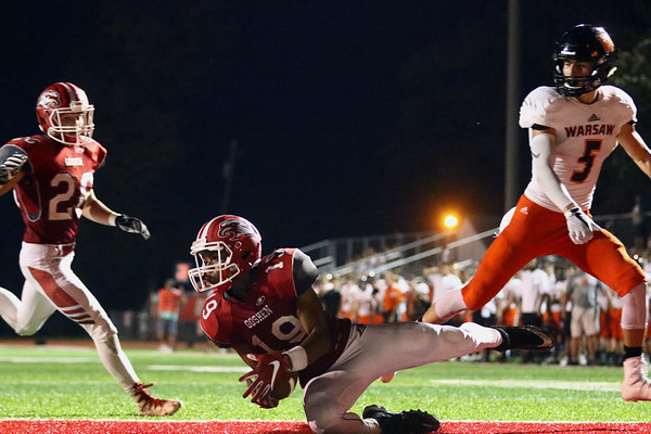 JAY YOUNG | THE GOSHEN NEWS<br /> Goshen High School senior Dominick Swinney (19) pulls down an interception in the end zone in front of Warsaw High School senior Zach Riley (5) during their game Friday night at GHS.