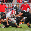 CHAD WEAVER | THE GOSHEN NEWS<br /> NorthWood defenders Ethan Hochstapler (42), Evan Bone (32), and Will Ingle (47) bring down Goshen quarterback Wesley VanHooser in the backfield during the second quarter of Friday night's game at NorthWood.
