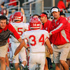 CHAD WEAVER | THE GOSHEN NEWS<br /> Goshen running back Liam Morales (34) is congratulated by Goshen assistant coach Kevin Park and head coach Kyle Park after scoring a touchdown during the second quarter of Friday night's game at NorthWood.