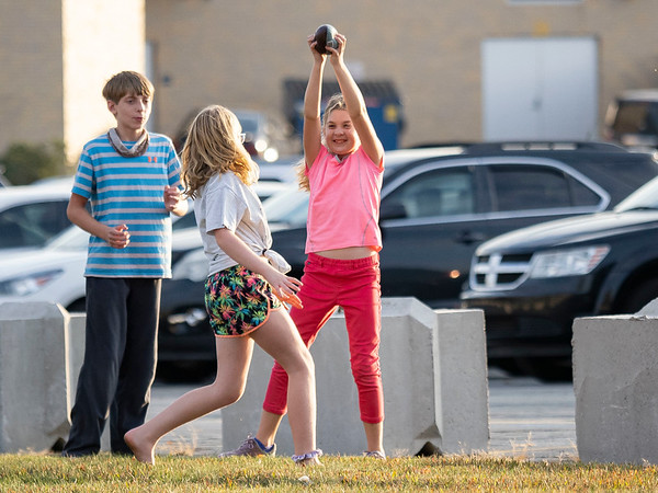 Kaitlyn Zehre, 9, right, of Eureka, Illinois, catches the ball while tailgating before Friday's game at Fairfield High School Jr./Sr. High School in Goshen.