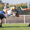 Wawasee Warriors Nathan Larson (20) leaps over Lakeland Lakers defensive back Mark Burlew (7) while his teammate defensive back Cole Schiffli (6) tries to block during the game between the Wawasee Warriors and the Lakeland Lakers Friday at Lakeland High School.
