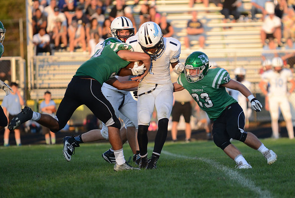 HALEY WARD   THE GOSHEN NEWS <br /> Concord linebackers Dominick De Broka (34) and Ryan Cook (33) tackle Saint Joseph running back Courtney Rowell Friday at Concord High School.