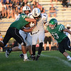 HALEY WARD | THE GOSHEN NEWS <br /> Concord linebackers Dominick De Broka (34) and Ryan Cook (33) tackle Saint Joseph running back Courtney Rowell Friday at Concord High School.