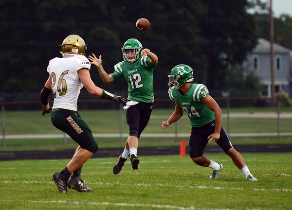 HALEY WARD | THE GOSHEN NEWS <br /> Concord quarterback Jack Lietzan passes the ball while Concord running back Dominick De Broka blocks Wawasee linebacker Paul Mendoza Friday at Concord High School.