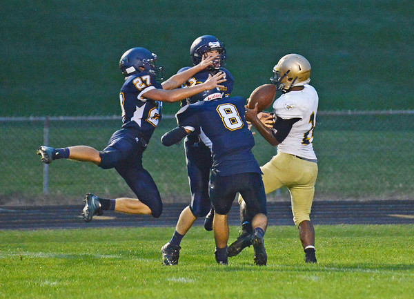 HALEY WARD | THE GOSHEN NEWS <br /> Fairfield defensive backs Tristin Ritter (27), Roger Burger (23) and Brady Willard (8) attempt to break up a pass to Niles running back Cameron Haines Friday at Fairfield Junior-Senior High School. Haines caught the ball and scored on the play.