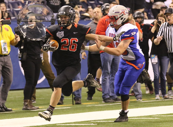 JAY YOUNG | THE GOSHEN NEWS <br /> NorthWood junior Brayton Yoder holds off Indianapolis Roncalli's Christian Bueggemann (49) as he races down the sideline and into the endzone during the 4A state championship game Friday afternoon at Lucas Oil Stadium in Indianapolis.