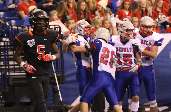 JAY YOUNG | THE GOSHEN NEWS <br /> NorthWood junior DeAndre Smart (5) walks to the sidelines as Indianapolis Roncalli players celebrate a touchdown during the 4A state championship game Friday afternoon at Lucas Oil Stadium in Indianapolis.