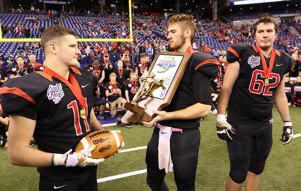 JAY YOUNG | THE GOSHEN NEWS <br /> NorthWood captains Drew Minnich (11), Trey Bilinski, middle, and Caleb Newcomer (62) stand withtthe runner up trophy following the 4A state championship game Friday afternoon at Lucas Oil Stadium in Indianapolis.