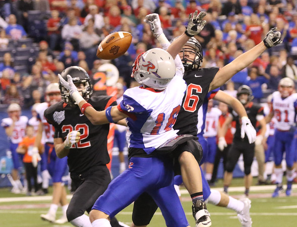 JAY YOUNG | THE GOSHEN NEWS <br /> NorthWood junior Brayton Yoder, right, breaks up a pass intended for Indianapolis Roncalli's Jacob Luedeman (16) during the 4A state championship game Friday afternoon at Lucas Oil Stadium in Indianapolis.