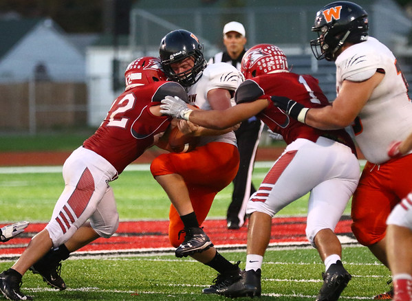 JAY YOUNG | THE GOSHEN NEWS<br /> Warsaw High School running back Bryce Garner takes a hard hit from Goshen High School linebacker Ian Hostetler (42) during their game Friday night at GHS.