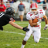 CHAD WEAVER | THE GOSHEN NEWS<br /> Goshen running back Liam Morales tries to avoid NorthWood linebacker Jake Lone after taking a handoff during the first quarter of Friday night's game at NorthWood.