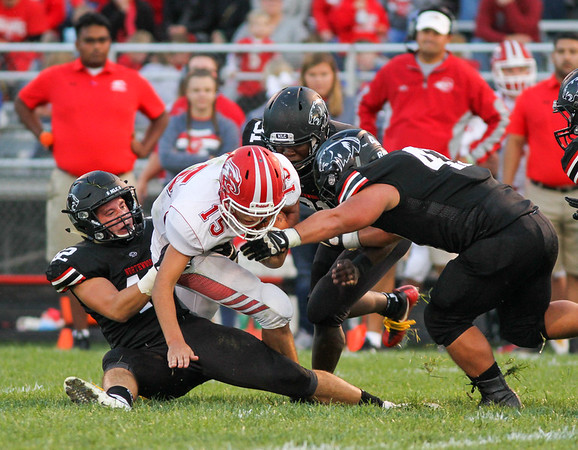 CHAD WEAVER   THE GOSHEN NEWS<br /> NorthWood defenders Ethan Hochstapler (42), Evan Bone (32), and Will Ingle (47) bring down Goshen quarterback Wesley VanHooser in the backfield during the second quarter of Friday night's game at NorthWood.