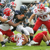 CHAD WEAVER | THE GOSHEN NEWS<br /> Redskin defenders #53, #49, and #90 wrap up Elkhart Central RB Joe Phillips on a carry during the first quarter of Friday night's game at Central.