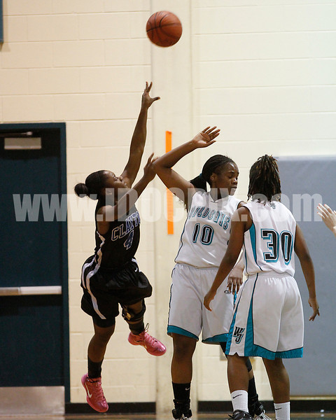 Clayton's Tajah Clark (4) puts up an off balance shot against West's Eboni Robinson (10) and Jarmelia Holder (30). The Clayton girls won the Greater Neuse River Conference game 74-43 held at West Johnston High School on February 7, 2012. Photo by Dean Strickland OD.
