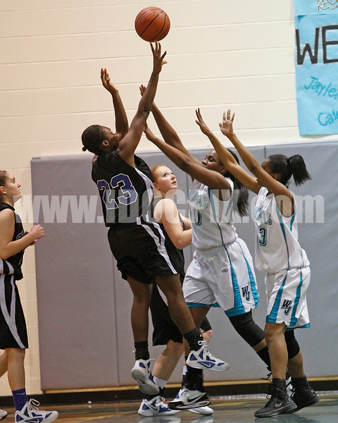 Clayton High's Jasmine Dixon (23) gets off a shot as West Johnston's Eboni Robinson (10) and Avvette Smith (23) defend the play. The Clayton girls won the Greater Neuse River Conference game 74-43 held at West Johnston High School on February 7, 2012. Photo by Dean Strickland OD.