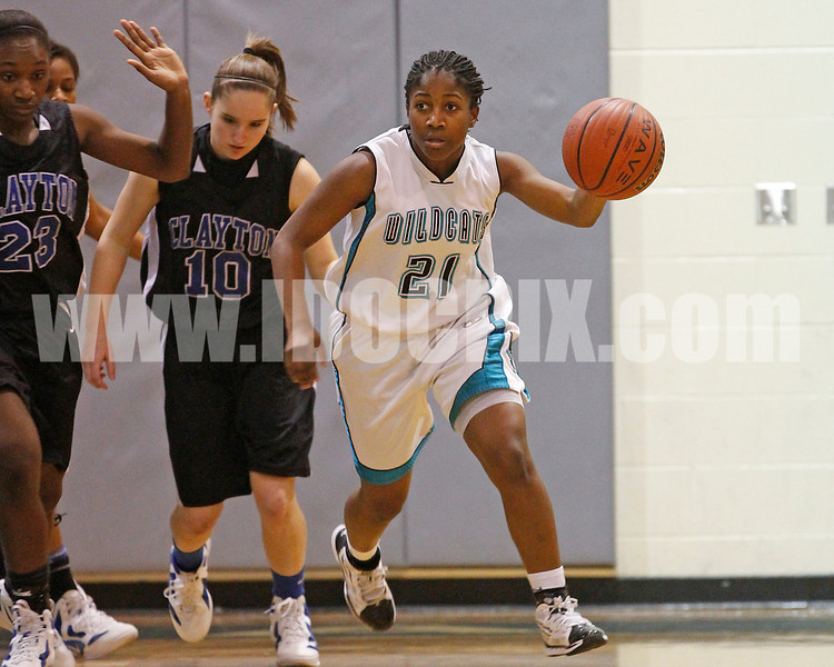 West Johnston's Shorty Frederick (21) brings the ball upcourt as Clayton's Jasmine Dixon (23) and Jenna Harris (10) pursue the play. The Clayton girls won the Greater Neuse River Conference game 74-43 held at West Johnston High School on February 7, 2012. Photo by Dean Strickland OD.