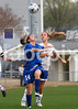 East Wake's Anna Riddle (14) heads the ball away from Clayton's Claudia Woznichak (14).