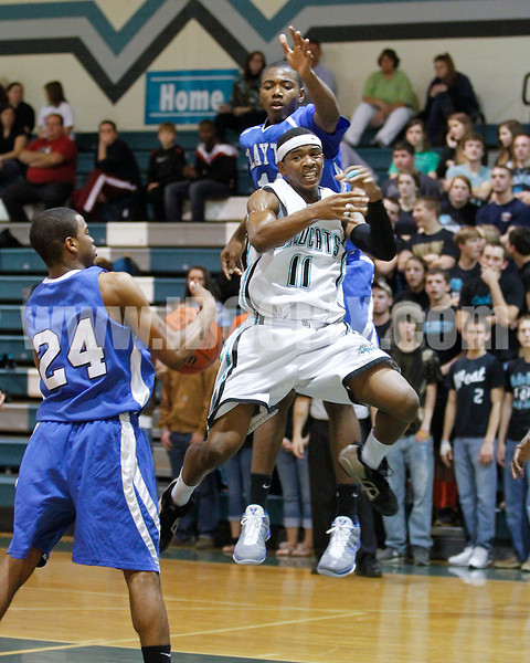 West's Darius Williams (11) gets fouled as he goes to the basket against Clayton's Adonis Banks (24) and Gary Clark (11). Clayton won the Greater Neuse River Conference game 53-42 held at West Johnston High on February 7, 2012.  Photo by Dean Strickland OD.