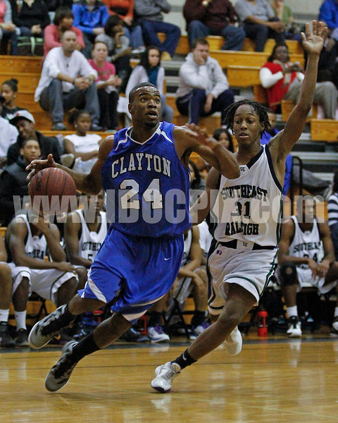 Clayton's Adonis Banks (24) heads to the basket as Southeast Raleigh's Derrick Snipes tries to defend.  Clayton won the Greater Neuse River Conference game 58-48  played at Southeast Raleigh High. Photo by Dean Strickland OD.
