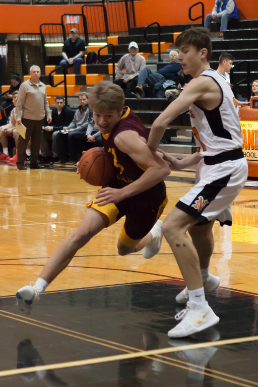 . Jen Forbus - The Morning Journal<br> Avon Lake\'s Cole Schraff puts his head down to drive the lane around Invader Alex Dugan on Jan. 2.
