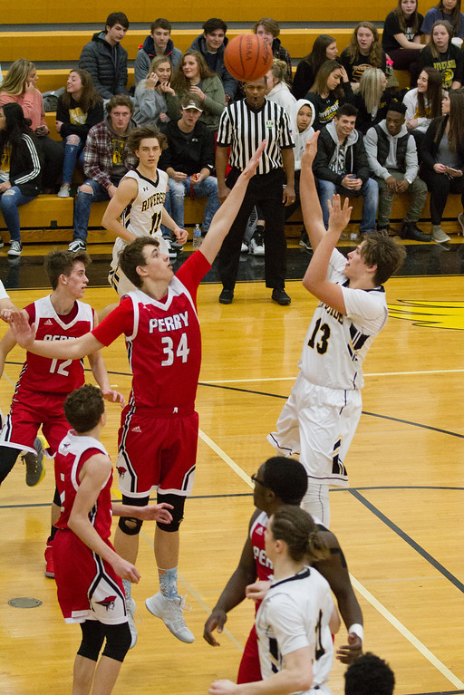 . Barry Booher- The News-Herald Riverside\'s Nate Sleek shoots over Perry\'s Matthew Cool on Jan. 13.