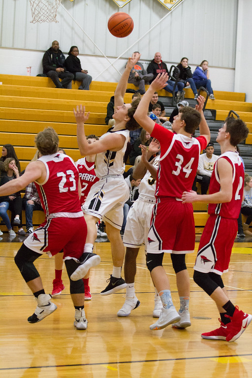 . Barry Booher- The News-Herald Riverside\'s Andrew Keller flips up a shot in a crowd of Perry defenders on Jan. 13.