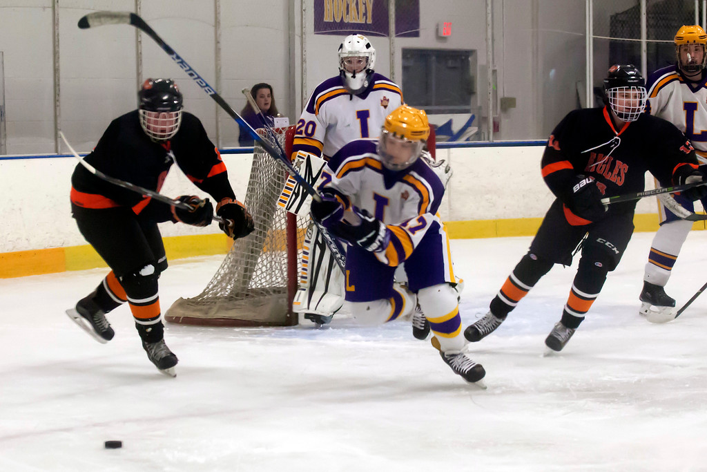 . Jen Forbus - The Morning Journal<br> Lakewood\'s Alex Blinky and North Olmsted\'s Jake Hirz race for the puck on Jan. 14.