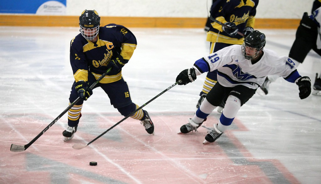 . Randy Meyers - The Morning Journal<br> Jacob Kerkay of Olmsted Falls moves the puck away from Jonathan Rodgers of Midview near center ice during a Southwestern Conference tournament semifinal on Jan. 15.