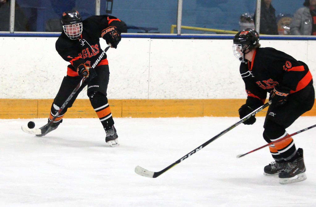 . Randy Meyers - The Morning Journal<br> North Olmsted\'s Jake Hirz passes the puck to Travis Vitaz against Amherst during a Southwestern Conference tournament semifinal on Jan. 15.